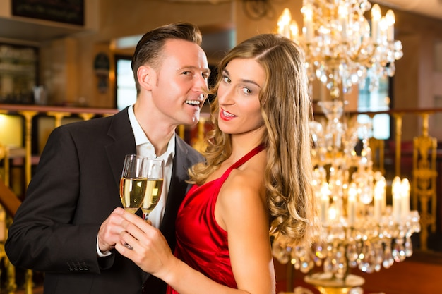 Couple, man and woman, drinking champagne in a fine dining restaurant, each with glass of sparkling wine in hand, a large chandelier is in