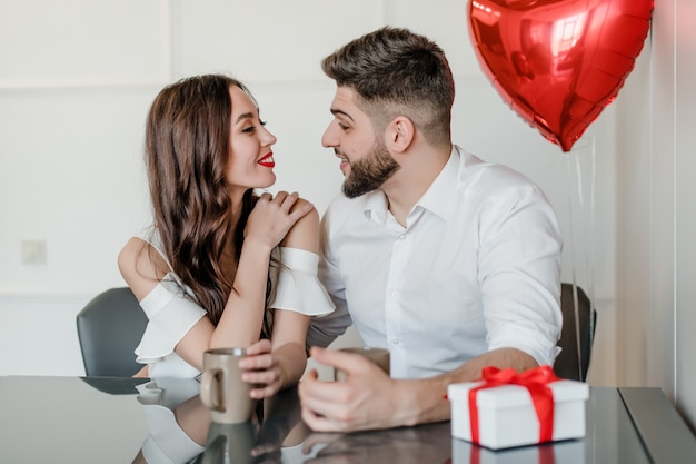Couple man and woman drinking from cups in the morning with present in gift box and heart shaped balloons at home