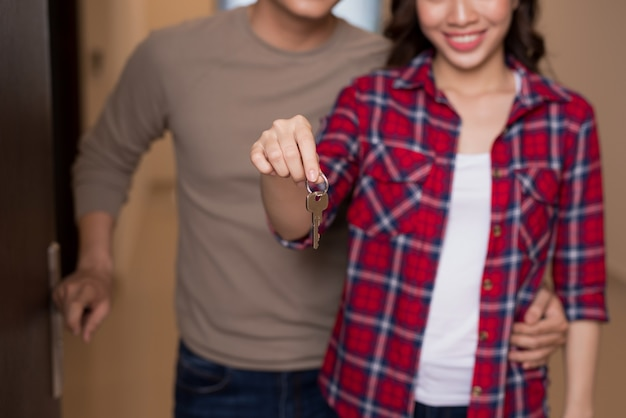 Couple man and woman handing their new home keys in front of an open house door