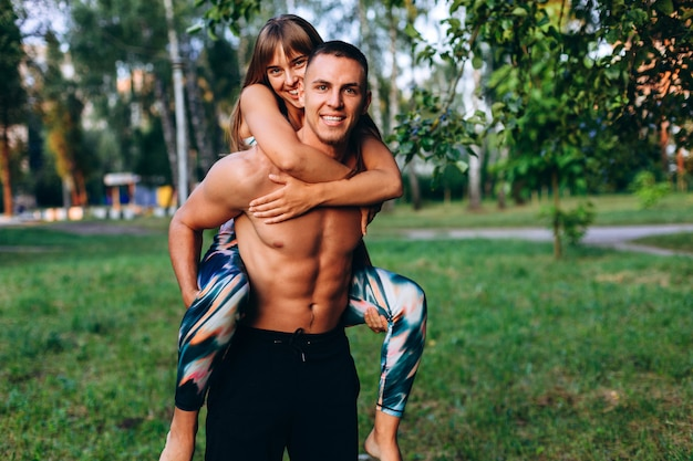 Couple man and woman have a fun time in the park outdoor. girl hugging a guy behind