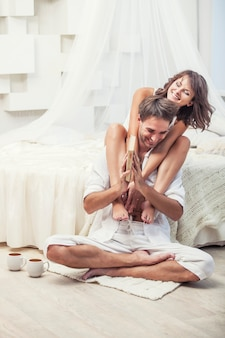 Couple man and woman at home in bed with a book and hot drink. tender love in family relationships