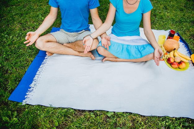 Couple man and woman sitting on the meadow with green grass in the lotus position. meditate in peace and freedom.