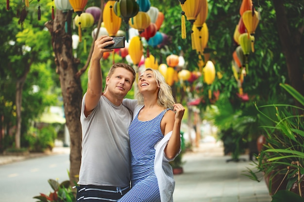 Couple a man and a woman take a selfie on a smartphone together on the street of an asian city happy and beautiful