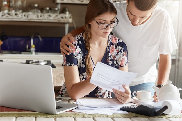 Couple managing budget together in kitchen