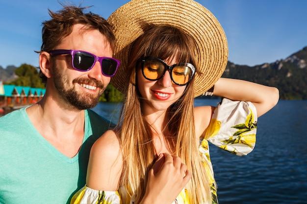 멋진 옷과 액세서리를 입고 놀라운 호수와 산보기 근처에서 셀카를 표시하는 커플. 장난기 가득한 행복한 분위기.