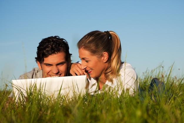 Couple on meadow using wi-fi