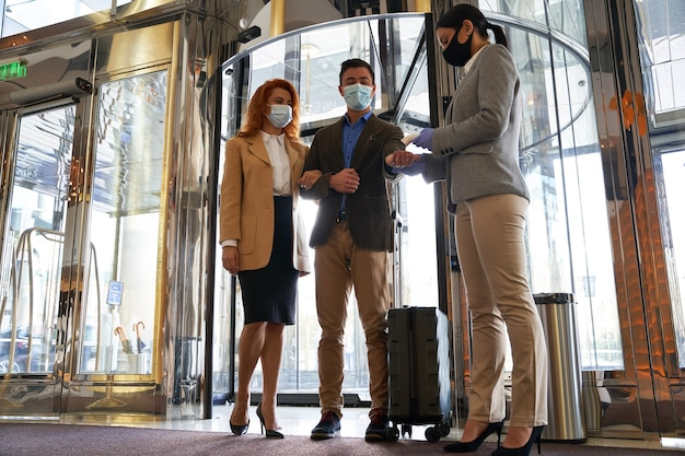 Couple in medical masks entering the hotel lobby and an administrator checking their temperature with contactless thermometer
