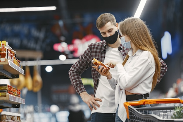 Couple in medical protective mask in a supermarket.