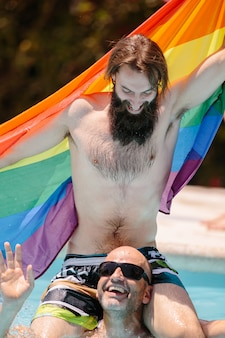 Couple of men in a pool on top of each other playing with an lgtb flag