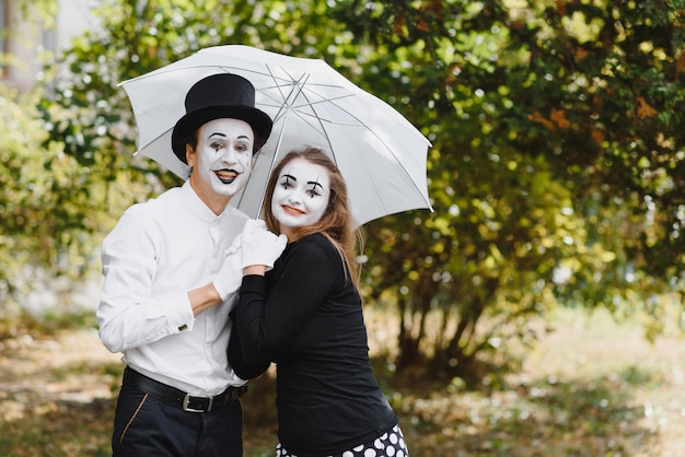 A couple of mimes walk along the pavement under umbrellas.