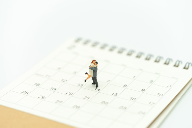 Couple miniature 2 people standing on calendar