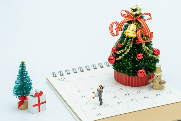 Couple miniature 2 people standing on christmas tree celebrate christmas