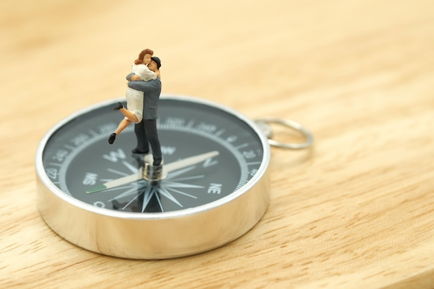 Couple miniature 2 people standing on a  compass