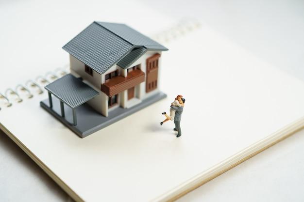 Миниатюрная пара 2 человека стоя модели с моделью дома делают семью чувствовать себя счастливой.