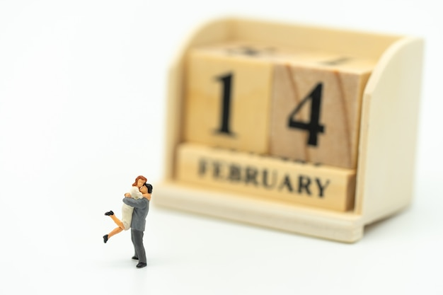 Couple miniature 2 people standing on white background. day 14 meets valentine day.