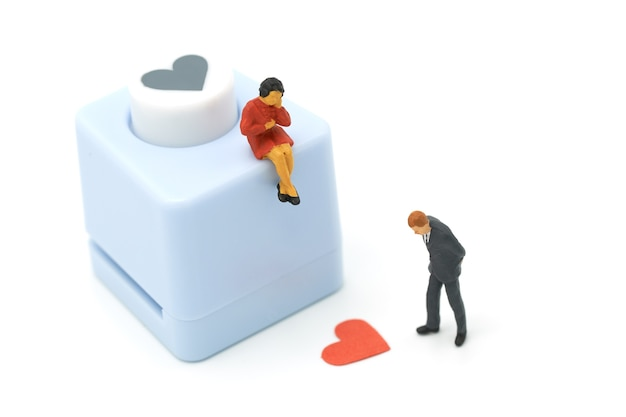 Couple miniature 2 people standing with heart shaped punching machine