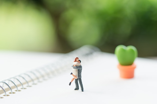Couple miniature people standing on book.