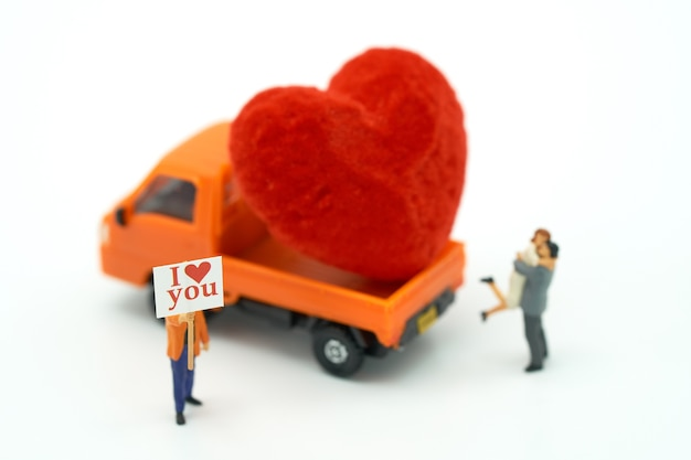 Couple miniature people standing with red heart