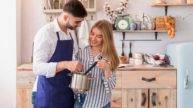 Couple mixing something in pot
