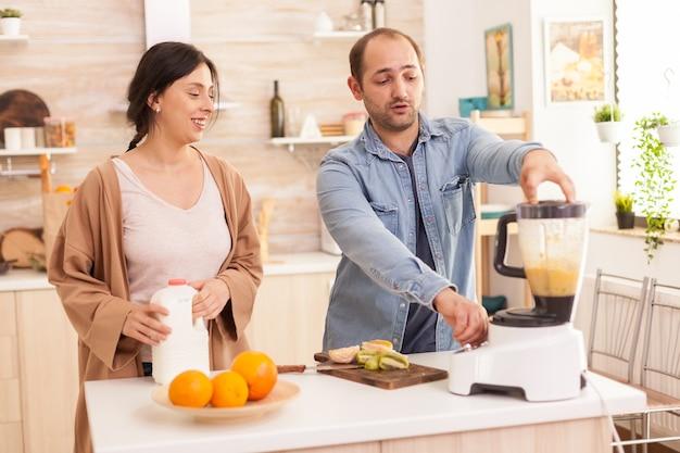 영양가 있고 건강한 스무디를 위해 다양한 과일을 섞는 커플. 건강하고 평온하고 쾌활한 생활 방식, 다이어트를 먹고 포근하고 화창한 아침에 아침 식사를 준비합니다.