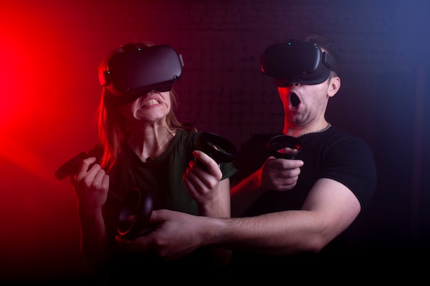 Couple in modern glasses of virtual reality play a shooter against a dark neon background, a team of gamers in a game with weapons