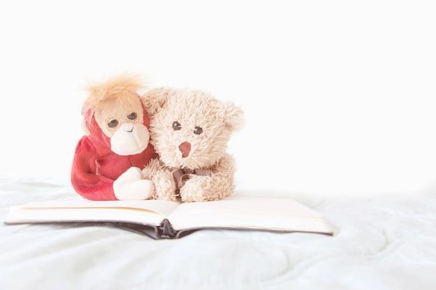 Пара обезьяны и плюшевого медведя с книжным чтением для экзамена
