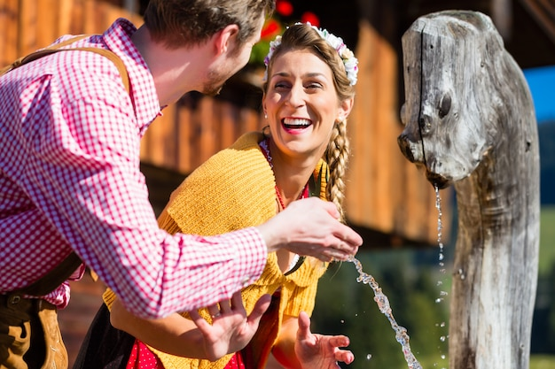 Couple at mountain hut drinking water from source