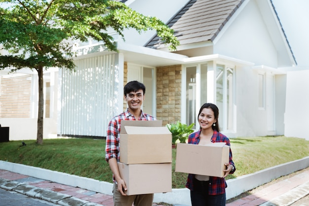 Couple moving to their new house holding cardboard box