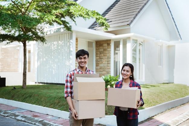 段ボール箱を持って彼らの新しい家に移動するカップル