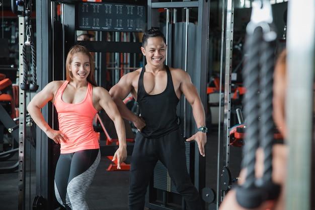 몇 근육 남자와 여자는 거울 앞에서 포즈