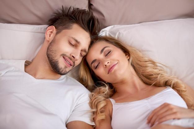 寝室で昼寝をしているカップル