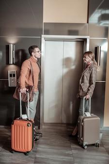エレベーターの近くのカップル。ホテルの部屋に向かっている間、荷物を持ってエレベーターの近くに立っているスタイリッシュなカップル