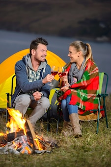 Couple near a fire while camping drinking wine together.