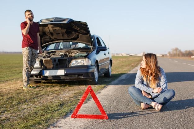 彼のブロッケン車の近くのカップル、警告サインとして赤い三角形、男性は開いたフードの前に立ってレッカー車を呼び出す