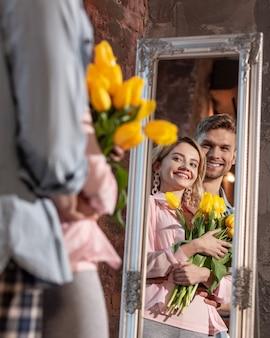 鏡の近くのカップル。鏡を見て明るく朗らかな新婚夫婦が大きく笑う