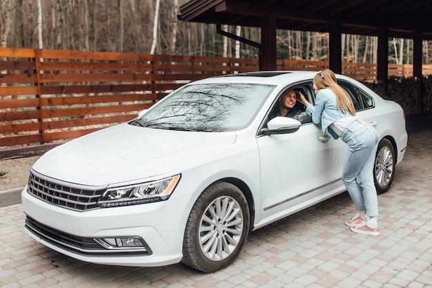 새 흰색 차 근처 커플입니다. 직장으로 운전하는 남자와 그의 아내가 그를 기다리고 있을 것입니다.