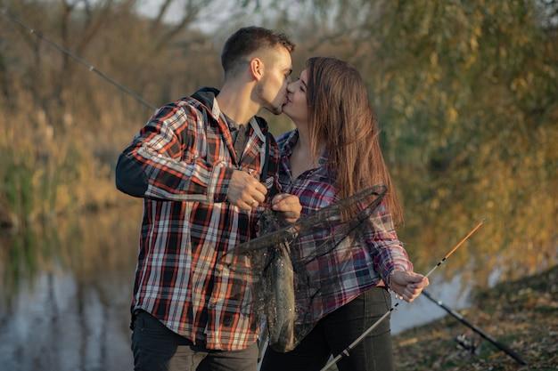 釣りの朝に川の近くのカップル