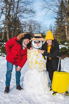 Пара возле снеговика с чемоданом, готовым для тропических стран