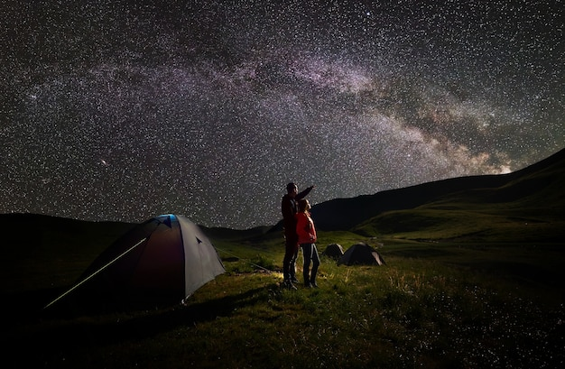 별이 빛나는 하늘 아래 텐트 근처 커플