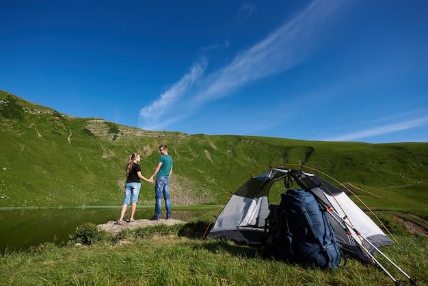 Пара возле туристической палатки, наслаждаясь в горах
