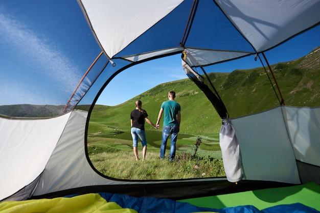 Couple near tourist tent enjoying in the mountains