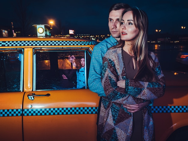 Couple near yellow taxi car in night time on the street of the city