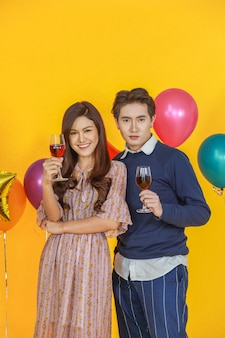 Couple, new year, valentine and holiday seasoning concept.  portrait of handsome asian man and  beautiful woman standing and holding red wine glass  with yellow background and colorful party balloon.