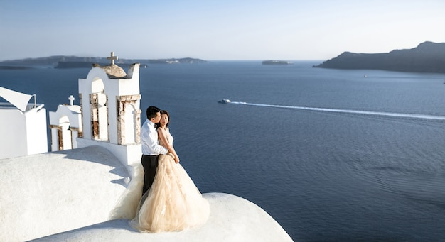 A couple of newly married people in beautiful attire enjoying their honeymoon months in greece