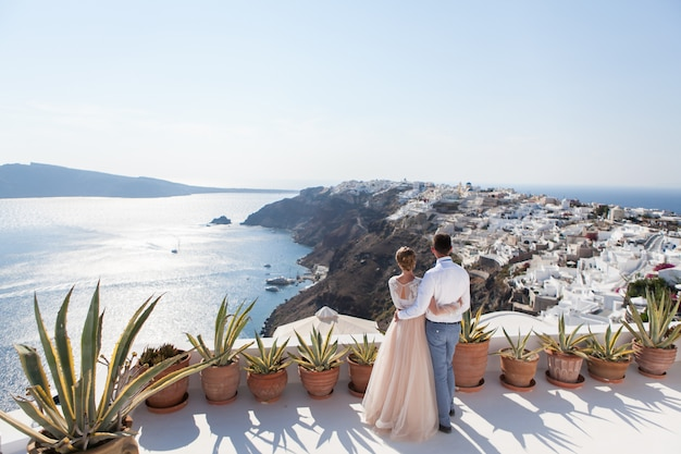 A couple of newly married people enjoying their honeymoon months in greece on the terrace over sea