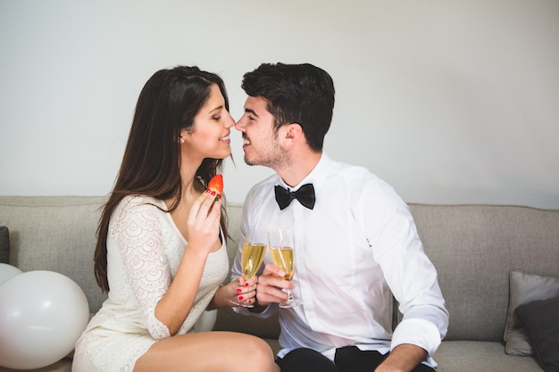 Couple nose with nose holding glasses of alcohol