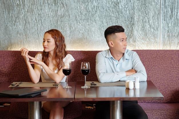 レストランのテーブルに座って別の方向を見ている議論の後に話していないカップル