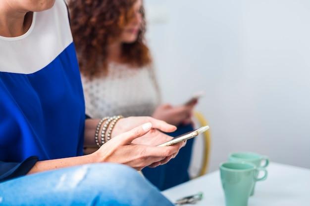 2人の女性の友人のカップルは、笑顔で楽しんでソファの上で一緒に近くにいます。コンセプトを生きるための素敵なライフスタイルの方法で屋内での友情や関係。電話でのメッセージング