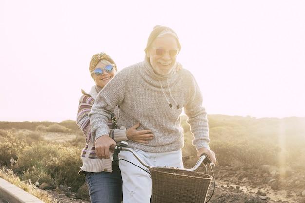 アクティブな陽気で幸せな高齢者の引退した人々のカップルは、バックライトで太陽と屋外のレジャー活動で一緒に自転車に乗ることを楽しんでいます-老後の概念と無制限の楽しい楽しい