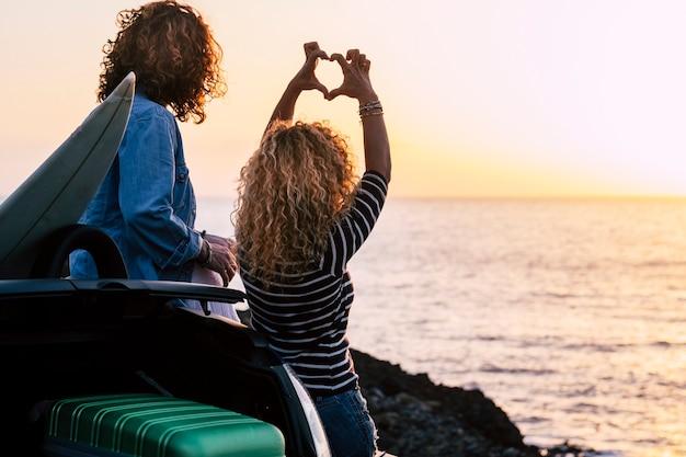 활동적인 젊은 여자 여자 친구의 커플은 함께 바다 수평선을보고 여름 일몰을 즐길 수